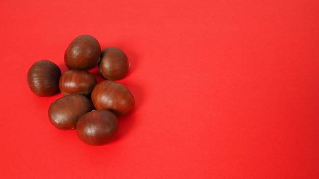 Gruppo di castagne da vicino su sfondo rosso.