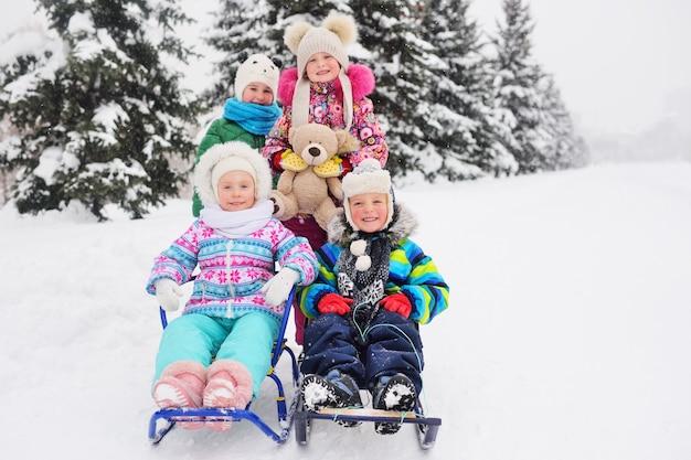 Un gruppo di bambini in abiti invernali dai colori vivaci su una slitta con i giocattoli nelle loro mani sorride