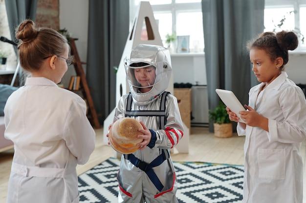 Gruppo di bambini in costume che recitano mentre giocano agli astronauti