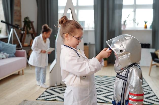 Gruppo di bambini in costume che giocano insieme nella stanza mentre eseguono un gioco
