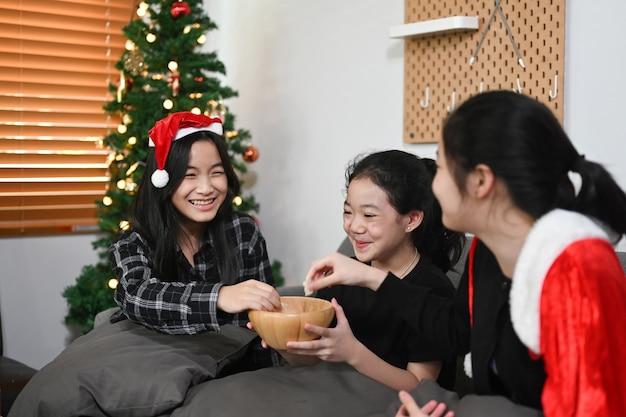 Gruppo di bambini che mangiano patate fritte per celebrare la vigilia di natale a casa.
