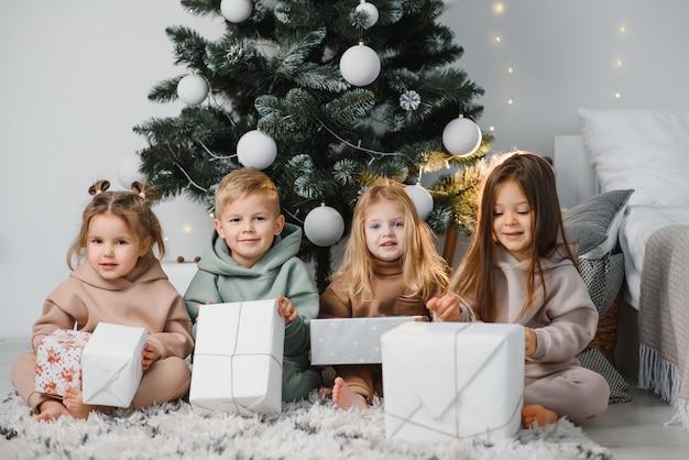 Un gruppo di bambini fa regali ai loro amici la mattina di natale seduti per terra in soggiorno sullo sfondo degli alberi di natale. concetto di scambio di regali per natale.