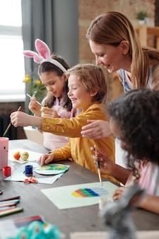 Gruppo di bambini che imparano a dipingere quadri insieme all'insegnante durante la lezione d'arte