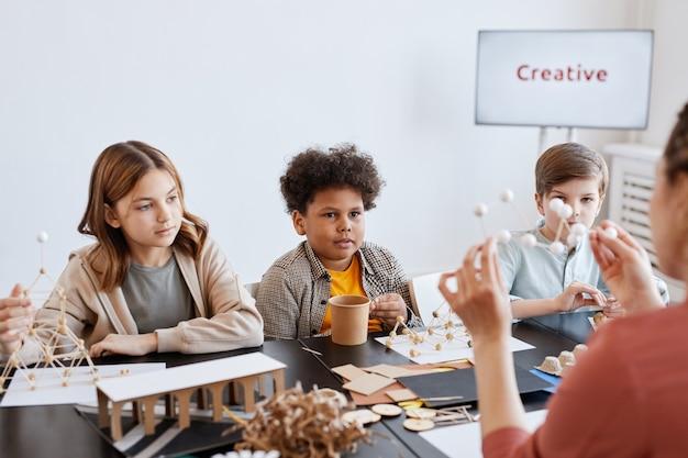 Gruppo di bambini che guardano un'insegnante che mostra modelli in legno durante le lezioni di arte e artigianato a scuola