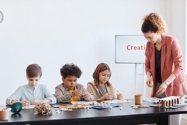 Gruppo di bambini che realizzano modelli di cartone durante la lezione di arte e artigianato a scuola con insegnante femminile