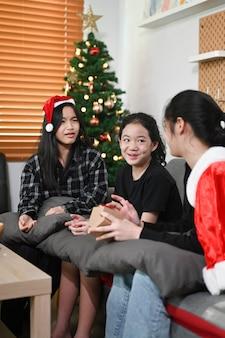 Gruppo di bambini seduti vicino all'albero di natale a casa.