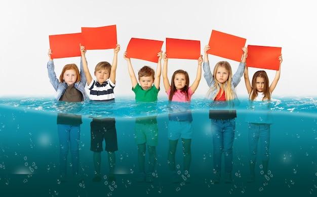 Gruppo di bambini con striscioni rossi vuoti in piedi nell'acqua del ghiacciaio in fusione, riscaldamento globale