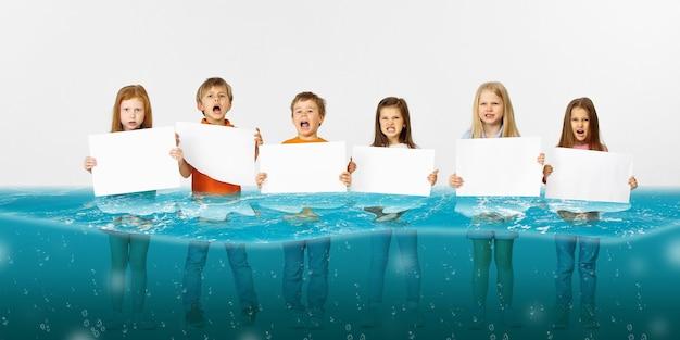 Gruppo di bambini con striscioni bianchi vuoti in piedi nell'acqua del ghiacciaio in fusione, riscaldamento globale