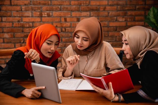 Gruppo di studente universitario, amici con tavoletta digitale e portando un libro