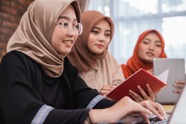 Gruppo di studente universitario, amici con laptop, tavoletta digitale e libri