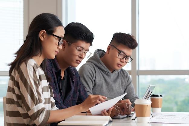 Gruppo di studenti universitari che bevono caffè e leggono documenti di progetto alla scrivania in classe
