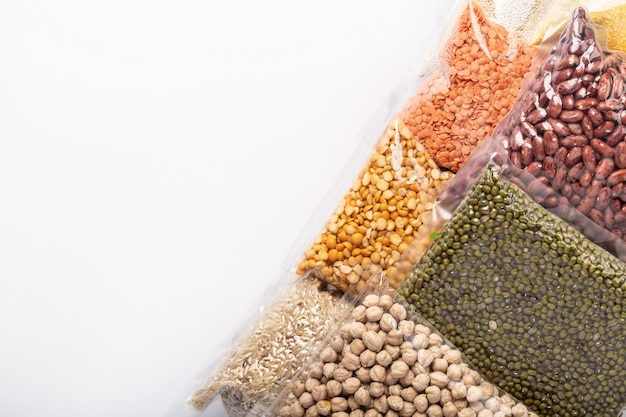 Gruppo di vari cereali e legumi variopinti in involucro di plastica sulla parete bianca con copyspace.