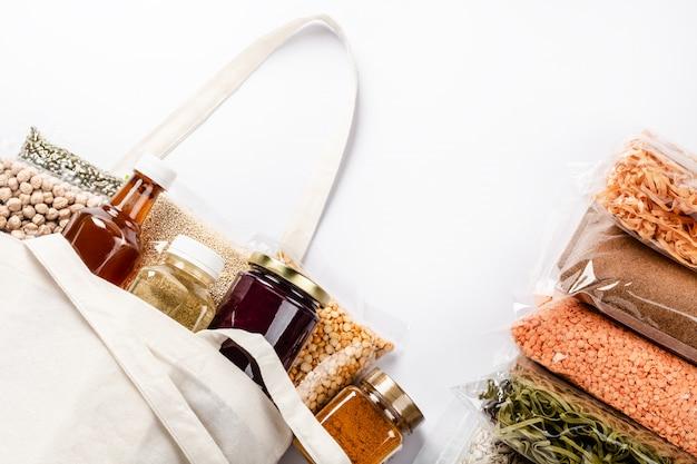 Gruppo di vari cereali colorati, semi, noci e legumi in involucro di plastica.