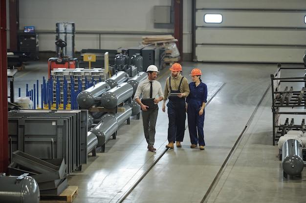 Gruppo di tecnici professionisti contemporanei in abiti da lavoro che si muovono lungo l'officina dell'impianto industriale e discutono i dettagli del progetto