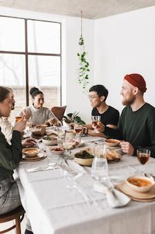 Gruppo di fantastici amici internazionali seduti a un tavolo pieno di cibo a parlare pensieroso insieme