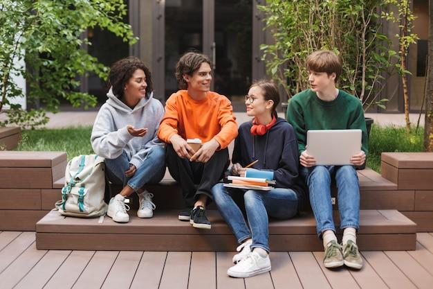 Gruppo di studenti sorridenti freddi seduti e guardandosi l'un l'altro felicemente mentre trascorrono del tempo insieme nel cortile dell'università