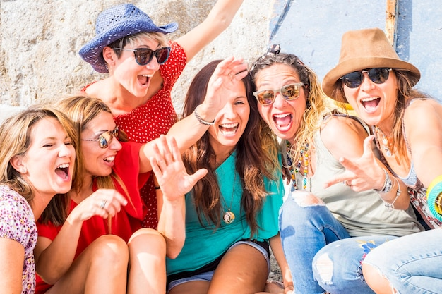 Gruppo di belle ragazze caucasiche belle pazze all'aperto sotto il sole estivo che fanno una festa tutti insieme. persone che si divertono insieme allo stile di vita. gridare e ridere pieno di donne gioiose