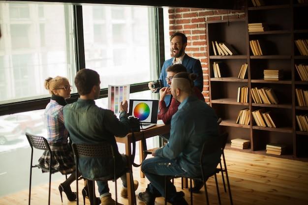 Gruppo di designer creativi che discutono di una nuova tavolozza di colori sul posto di lavoro in un ufficio moderno