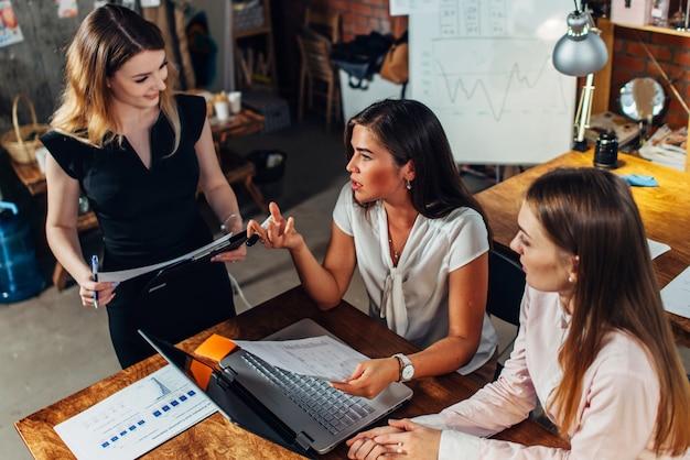 Gruppo di designer femminili creative che lavorano insieme a un nuovo progetto parlando.