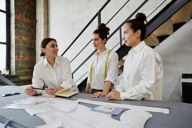 Gruppo di designer di moda moderni creativi in camicie bianche che discutono di idee per la nuova collezione stagionale alla riunione