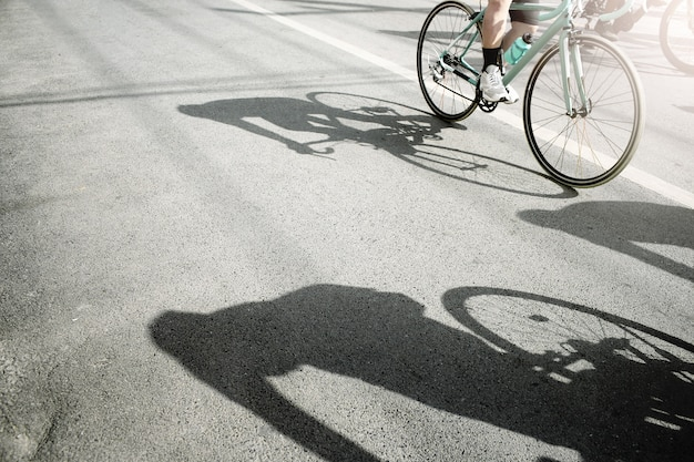 Gruppo di ciclisti che pedalano su una bici da corsa con ombra dura in una giornata di sole.