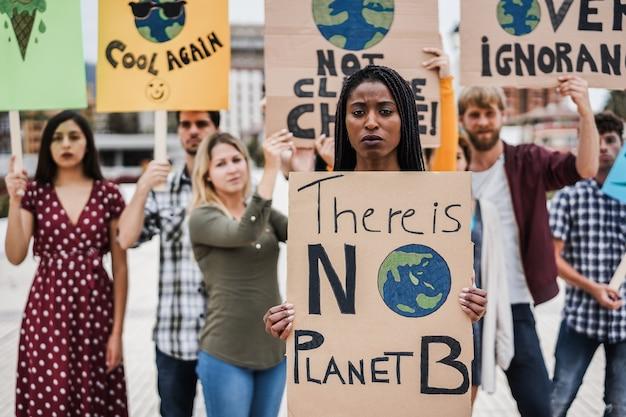 Gruppo di manifestanti su strada, giovani di culture diverse lottano per il cambiamento climatico