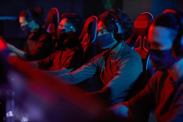 Gruppo di sviluppatori in maschere protettive seduti davanti ai computer e lavorano in ufficio buio