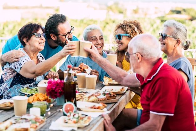Gruppo di persone di età diverse festeggiano e mangiano insieme all'aperto