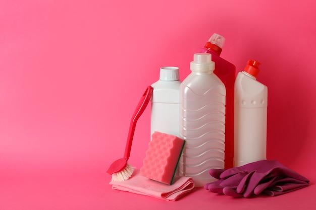 Gruppo di diversi strumenti di pulizia su sfondo rosa