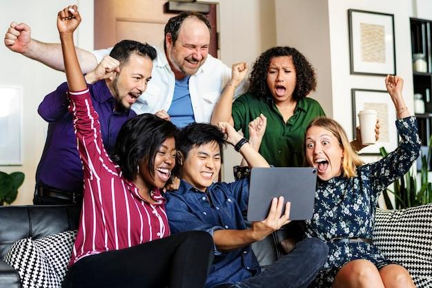 Gruppo di diversi uomini d'affari che guardano insieme un contenuto su un tablet digitale