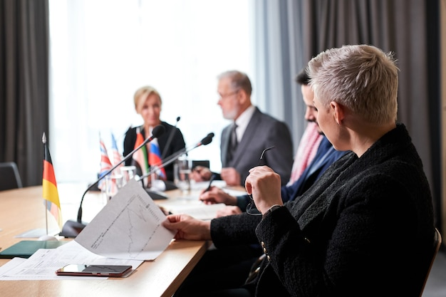 Gruppo di diversi uomini d'affari che lavorano e comunicano seduti alla scrivania insieme, discutendo idee di business. nella moderna sala riunioni