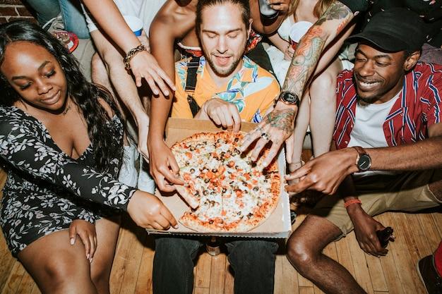 Gruppo di amici diversi che si godono la pizza a una festa
