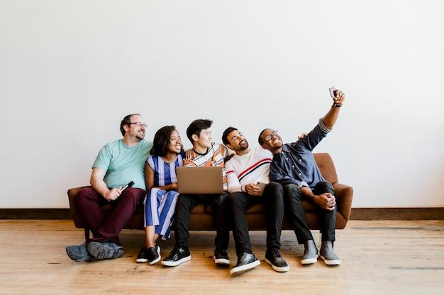 Gruppo di amici diversi che si fanno un selfie su un divano