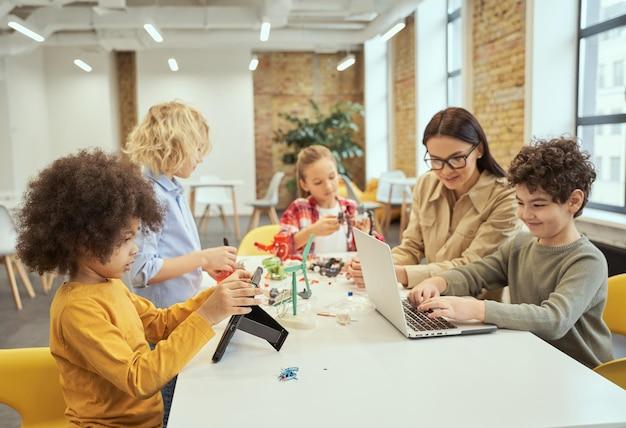 Gruppo di bambini diversi che lavorano insieme a una giovane insegnante utilizzando dispositivi digitali e giocando