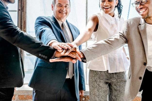 Gruppo di persone diverse che impilano le mani nel mezzo
