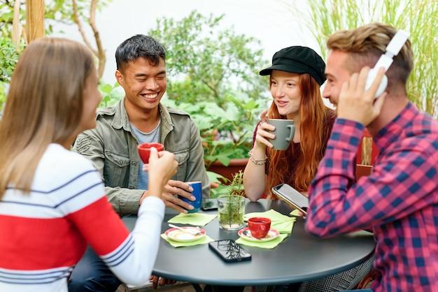 Gruppo di giovani studenti diversi che si godono una pausa rilassante seduti attorno a un tavolo all'aperto ridendo e scherzando mentre si gustano una tazza di caffè