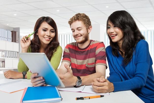 Gruppo di studenti di diversità che studiano facendo uso della compressa