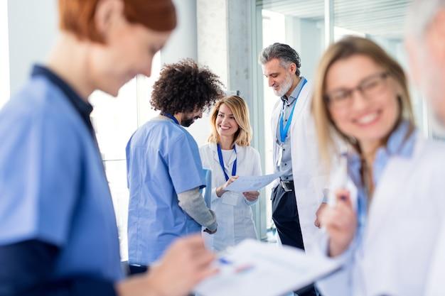 Gruppo di medici in conferenza, team medico in piedi e discutere di problemi.