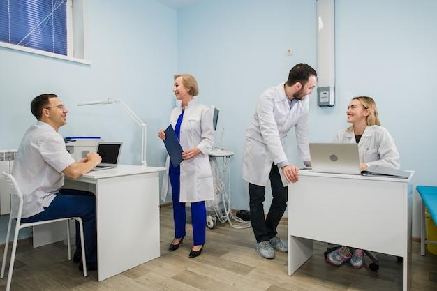 Gruppo di medici coinvolti in una seria discussione con le cartelle cliniche