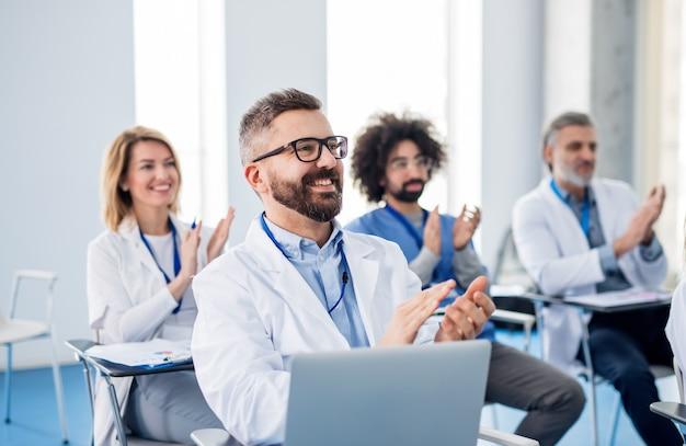 Un gruppo di medici che ascoltano la presentazione alla conferenza medica, applaudendo.
