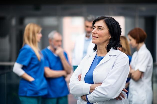 Un gruppo di medici in piedi nel corridoio dell'ospedale durante una conferenza medica.