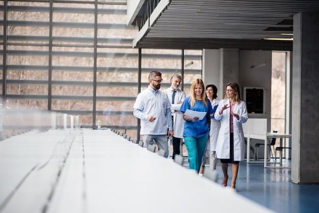 Gruppo di medici che camminano in corridoio durante una conferenza medica, parlando. Foto Premium