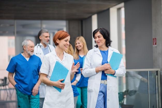Gruppo di medici che camminano in corridoio durante una conferenza medica, parlando.