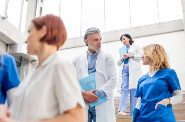 Gruppo di medici che scendono le scale durante una conferenza medica, parlando.