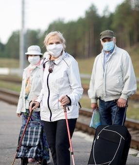 Gruppo di anziani anziani persone con maschere facciali in attesa del treno prima del viaggio