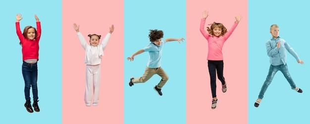 Gruppo di bambini o alunni delle scuole elementari che saltano in abiti casual colorati su uno studio bicolore