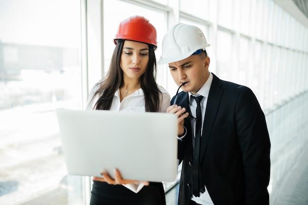 Gruppo di ingegnere uomo e donna in cantiere per verificare il nuovo progetto con il computer portatile. nuovo ingegnere di progetto fuori dal viaggio