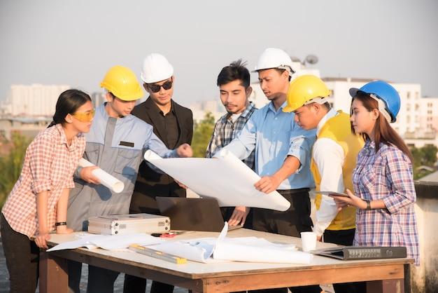 Gruppo di ingegneri e architetti discutere in un cantiere