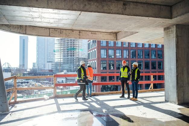 Un gruppo di ingegneri in piedi sul cantiere, parlando.