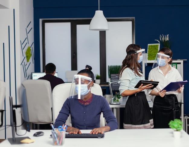 Gruppo di imprenditori che lavorano insieme indossando la maschera per il covid19. team aziendale multietnico che lavora rispettando la distanza sociale durante la pandemia globale con il coronavirus. Foto Premium